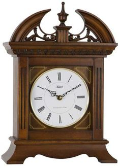 """From www.theisenclock.com 42011 - Hermle Jackson Mantel Clock - Formal bracket style mantel clock in a satin walnut finish. Fluted dual columns frame corner silkscreened elements on a fixed glass front. Formal pediment centered with a finial and a carved, open botanical motif which is removable to create two different styles.  Measures: H 15"""" x W 11"""" x D 6""""   Three year manufacturer's warranty    Free shipping within the contiguous United States"""