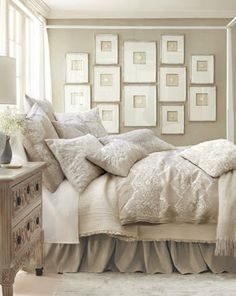 I love how the wall arrangement blends with the linen color scheme in this sedate sleeping room.