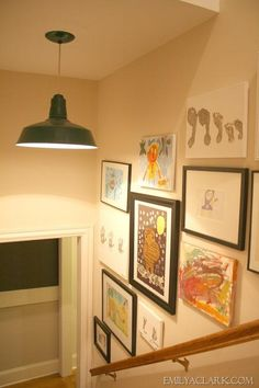 A unique pendant light and kids' artwork lining the walls make for a happy stairway!
