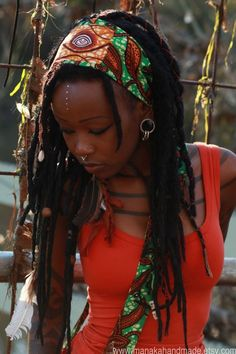 .Gorgeous dark skinned Black woman with locs, orange vibrancy top and African head band. Righteous