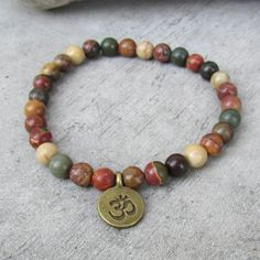 NETRA Ethnic bracelet for men, small pearls of stones Jasper, pendant Ohm bronze, bracelet of friendship, zen, meditation, gift This stretch bracelet in semi precious stone beads is a jewelry that can be worn every day Suit men or women. It will match with other bracelets you already have or that you can find in my shop, to perfect the stack of jewelry to your ethnic fashionable wrist. This mala style bracelet in semi precious pearls from Jaspe Picasso (beige, brown, green, burgundy)