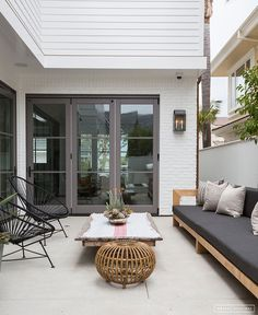 Modern, organic outdoor seating area with acapulco chairs and sofa with wood, rattan, and black and white accents. Backyard/outdoor patio entertaining.