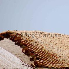 Le tegole, in siciliano ciaramìre, sono fatte di una miscela di terra che cuoce nel fuoco vivo. Dopo questo crogiolo sono pronte a sfidare il sole, per proteggere il lavoro svolto nelle saline. La luce che le taglia di traverso riesce solo a fare esaltare gli spessori della loro materia.