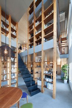 Rows of wooden pillars support various split-level floors to create a…