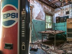 Image: Inside an abandoned asylum (© BARCROFT MEDIA/Johnny Joo)A Pepsi coke machine stands under a broken ceiling in the lounge.