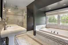Extensive marble throughout this luxury bathroom in white grey and black color scheme. Tub sits in own nook under windows. 2 separate standing basins and separate shower make up the rest of this luxury bathroom.