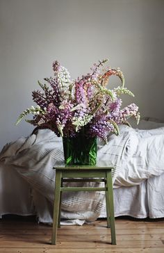 large bouquet of rose and violet hues, vase on small table in bedroom, photographed with beautiful natural light
