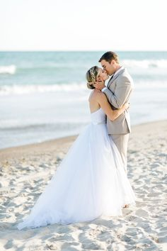 bride and groom photos at the beach. tule wedding dress. groom beige suit.
