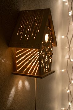 This little wooden birdhouse has been fitted with low-wattage candelabra bulb and drilled with a one-of-a-kind pattern, drawn by hand. Its glow is
