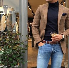 This combination of a brown wool suit jacket and baby blue jeans is perfect for a night out or smart-casual occasions. Shop this look on Lookastic: https://lookastic.com/men/looks/blazer-turtleneck-jeans/21397 — Brown Wool Blazer — Navy Pocket Square — Black Turtleneck — Brown Woven Leather Belt — Light Blue Jeans