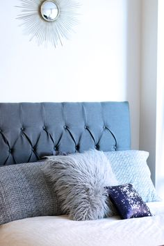 How to design a stylish bed: pick a relaxing color, combine different textures in similar hues and you've created a dream-worthy design! Seen here in gray is a tufted cotton headboard, thick woven pillows, accented with a fun faux fur and sequin pillow, and topped off with a metallic sunburst wall mirror.