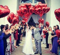 Balões metalizados de coração vermelho para as fotos dos noivos ficarem ainda mais lindas na saida da cerimônia religiosa ao lado dos seus queridos padrinhos.