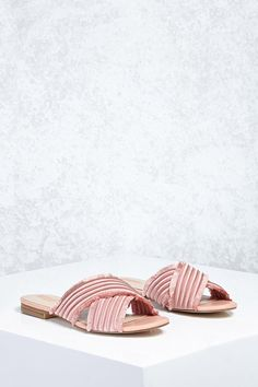 3393caf8ec5 A pair of satin slides featuring a crisscross padded upper with stitching  to create a ribbed design
