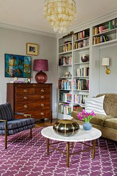 Angie Hranowsky Stocker living room, gray, purple, antique dresser, capiz shell, bookshelves, white marble brass table