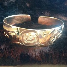 "AUTHENTIC 14K. YELLOW GOLD HAIDA CARVED BANGLE  MEASUREMENTS: Approximately 5/8"" (width) . Total weight 21.4 grams . Hand Carved by MASTER CARVER, Design on bangle is Love Birds, RAVEN AND EAGLE CLAN . I HAD THIS MADE FOR MYSELF IN HONOR OF MY GRANDPARENTS, I PAID FOR THE GOLD, AND THEN HAD TO PAY FOR THE MASTER CARVER'S LABOR. THIS PIECE IS BEYOND GORGEOUS . AT THIS POINT IN MY LIFE I AM FACING HEALTH ISSUES, LONG RECOVERY, MAJOR MEDICAL BILLS, SOMETIMES YOU JUST HAVE TO LET THING GO. IT…"