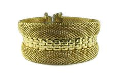 This Hobe gold tone mesh bracelet is offered for your consideration.  Composition: Flexible gold tone mesh surrounds a strip of heavier woven links to form the bracelet. The ends are finished with embossed metal caps, box clasp and safety chain.  Condition: Excellent vintage condition.  Signature: Hobe with accent over the e and no copyright symbol.  Measurements: 7 inches long, 1 inch wide.  Gift boxed.  NOTE: 16% Markdown taken 11/11/16.