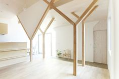 Wide Space Inside The House H With Wooden Pillars And White Ceiling Above The Wooden Floor