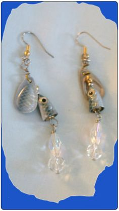 http://diginanchors.com/EarringsAlure_GreyMako - Hanging earrings made with a fishing lure with a small wide, beautifully painted grey spinner blade. Blade spins on the wire to draw the eye to the wearer. To enhance the beauty of the earrings ,a fire-polished, sparkling clear bead and clear crystal are added. The earring is 3 and 1/4 inches long. It is hung on surgical stainless steel earwires that are silver plated