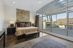 Modern master bedroom with large sliding glass door looking out to the deck view.