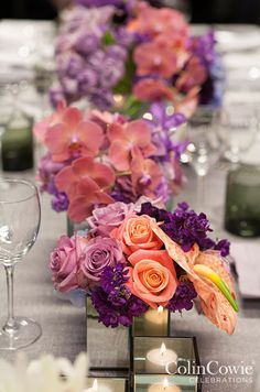 Bright floral arrangements shine when paired with candlelight and placed in reflective vessels. Low Centerpieces, Wedding tabletop, Flowers