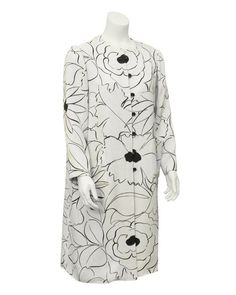 Early Nina Ricci piece, dating from the 1960's. Coat is white linen with a gorgeous print of outlined flowers in black. Floral print has a loose quality, looks as though it was sketched on the coat. Coat features bracelet length sleeves, seven buttons with corresponding loops down the front, and front pockets.