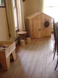 I admire the furniture in this picture. The sensory table is beautiful, and I love the two wooden stools at the little table. The house is lovely too, but I wonder, if it is big enough for my 4 & 5 year old kinders and/or enough light would get in to invite play.
