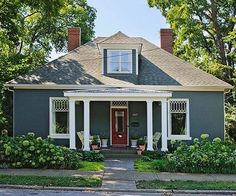 The front of the house now has a columned porch, a new front door, and a coat of blue-green paint over its tired maroon brick. Lush sidewalk plantings soften the front yard and better connect the house with its surroundings.