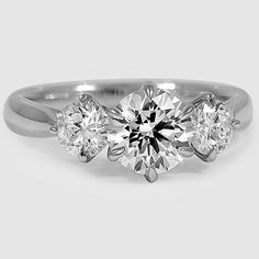 A three stone diamond engagement ring represents the past, present, and future.