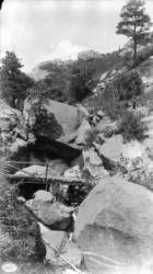 Sheltered Falls. Pike's Peak trail. View of a waterfall identified as Sheltered Falls with a pole bridge and woman on the back of a donkey, El Paso County, Colorado. Date [between 1882 and 1900?]. Creator(s): Jackson, William Henry, 1843-1942.  Courtesy: Western History/Genealogy Department, Denver Public Library, Denver, Colorado (USA).