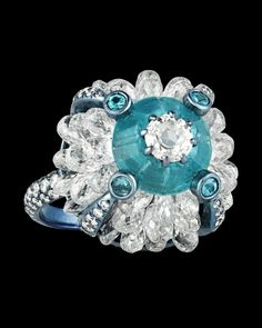 """Paraiba and Diamond Ring, 3.08 Carats~ This stylish ring boasts rare Paraiba tourmaline stones weighing 3.08 carats with 21.62 total carats of white diamonds. Evoking the popular evil eye motif — an ancient protective talisman — this ring's highly unique sculptural blue titanium setting features a brilliant blue Paraiba """"iris"""" and diamond """"pupil"""" at its center. ~M.S. Rau Gemstones For Sale, Rare Gemstones, Tourmaline Stone, Stylish Rings, Alexandrite, White Diamonds, Gemstone Colors, Evil Eye, Peridot"""