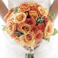 Succulents and leaves added texture to the mostly orange bouquet using traditional and spray roses.