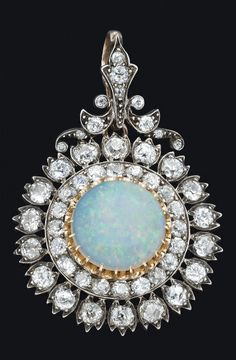 *A Victorian opal and diamond cluster pendant by West & Son, Dublin, c.1870. The central round white opal cabochon of estimated weight 2.60 carats in a stepped surround of old brilliant cut diamonds of estimated total weight 5.40 carats. Detachable brooch, pendant and hair piece fittings in original box. Yellow gold and silver.