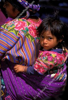 Zunil, Guatemala. A young girl sits contentedly in a sling of woven cloth on her mother's back. The two wear identical huipiles, with the typical pattern of multi-colored stripes
