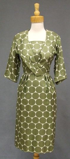 """A truly fun 1960's cocktail dress in ivory silk with oversized olive polka dots. 3/4 sleeved dress with dramatic collar and fitted skirt with rear center seam vent. Rear metal zipper. Lined. String belt loops but no belt. """"A Leslie Fay Original,"""" label."""