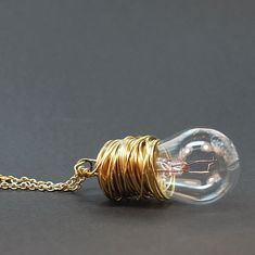 This found object necklace is made from a vintage auto light bulb wrapped in brass wire. The light bulb pendant is hung from a 20 brass colored chain. The hook and eye style clasp is gold plated. The light bulb pendant is about 2 long and 1 wide. This necklace is made to order, so there will