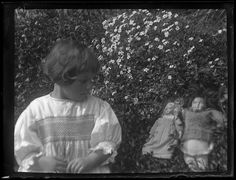 1900's girl with two dolls, one looks like a bisque head, the other may be compo