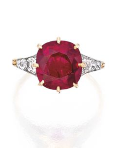 PLATINUM, GOLD, RUBY AND DIAMOND RING. Centered by a cushion-cut ruby weighing 4.36 carats, flanked by six old European-cut diamonds weighing approximately .30 carat, size 5¼; circa 1900.
