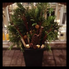One of my #DIY #Christmas planters. Recycled my black summer planters. How to: Select your own mix of greenery, branches, twigs, pine cones, ornaments and sparkle - randomly stick into planter with potting soil to your liking. Start with centre pieces and work your way out. Water and sprinkle with hot chillies to keep pests away.