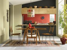 Angled Roof Line This Eclectic Kitchen Combines Dark Gray And Orange Walls With A Mid Century Modern Dining Table An Antique Oriental Rug