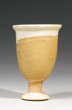 Egyptian Stone Vessel, 12th/19th Dynasty, 1938-1190 B.C. - A banded alabaster goblet with splayed foot convex underneath, short stem, and deep rounded body with flaring rim. Height 4 1/2 in.
