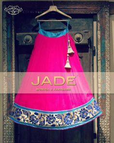Bright pink lehanga with blue and gold floral border. Jade by Monica and Karishma.