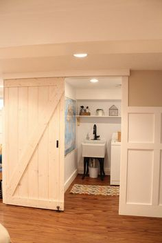 When this sliding barn door is closed you would never know that there is a laundry room right off of this home's entryway