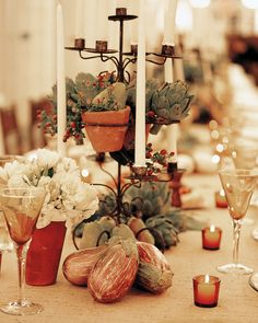 A spread of eggplants and artichokes casually arranged, as well as perched among tall candelabras, provides a natural vibe at a long reception table.