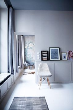 Living space with light gray walls, white floors and a knit armchair