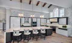 This gorgeous kitchen was featured in the January 2016 edition of HOME & DESIGN Magazine. To see other featured homes with stunning architecture, interior design, and landscaping visit http://www.homeanddesign.net/dream-house-prato-in-talis-park/ #naples #florida #kitchen #modern #white #black #neutral #hardwood #woodfloors #reclaimedwood #barstools #pendantlights #lighting #appliances #kitchenappliances #woodbeams #beams #white #fresh #interiordesign #architecture