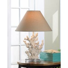 Stunning White Coral Table Lamp - A splash of seaworthy style to light up your life! This Stunning White Coral Table Lamp features artistically rendered ivory sprigs of coral topped with a handsome neutral-color shade. Turning on the lamp lights coral and your room with a warm and inviting glow.
