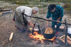 Kaduni, a Forest Nenets grandmother, cooking fish (roach) while her daughter-in-law Irina fries bannock, over a camp fire in the summer. Purovsky Region, Yamal, Western Siberia, Russia