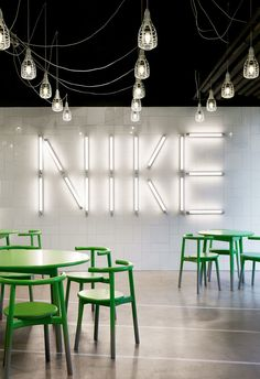 MC5 Solo Collection – Mattiazzi.Canteen. Breakout space. Nike. Green chairs. Hanging lights. Black ceiling.