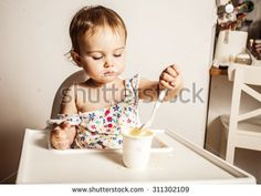 Cute baby girl one year old eating a yogurt by itself. - stock photo
