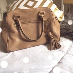 ⬇️REDUCED Michael Kors Purse Love this adorable nude handbag with its cute MK tassel. I used it for less than a season, so there's very minimal wear other than a few makeup marks inside, but MK purses lining cleans super easily. This purse comes with a long strap that can be attached as a satchel.  The loop broke, but can be easily fixed by a shoe repair person, i just never got around to it! Will trade for Rebecca Minkoff or Jack Rogers. Payed $375 originally. Thanks ! Michael Kors Bags